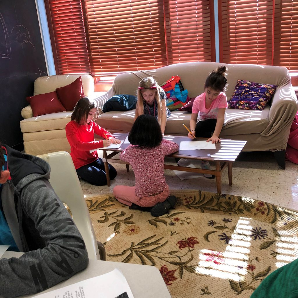 girls sitting around a table doing crafts